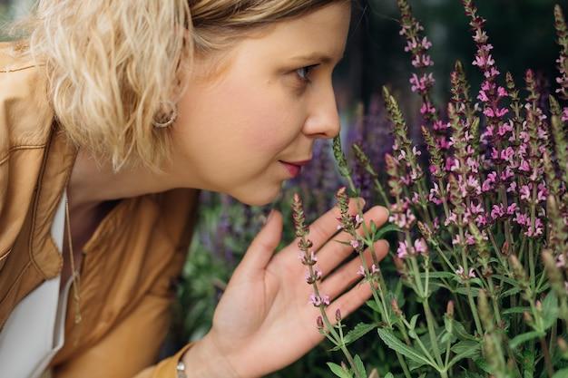 Młoda kobieta z przyjemnością pachnie pachnącymi kwiatami na oknie ulicy kwiaciarni. praca kwiaciarni. aromaterapia. zioła lecznicze i rośliny.