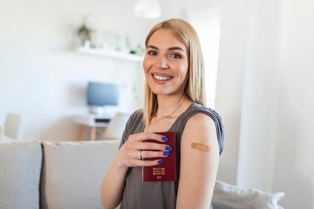 Młoda kobieta z przylepnym bandażem na ramieniu po szczepionce przeciwko wirusowi corona covid 19, trzymająca paszport. gotowy do podróży. pierwsza pomoc. pojęcie medycyny, farmacji i opieki zdrowotnej.