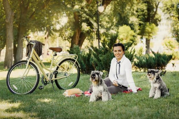Młoda kobieta z psami i bicyklem ma pinkin w parku