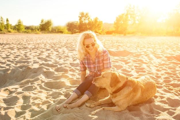 Młoda kobieta z psem na plażowym blasku słońca
