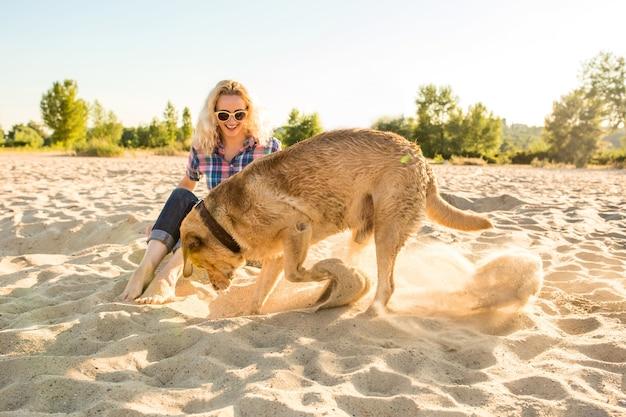 Młoda kobieta z psem na plaży