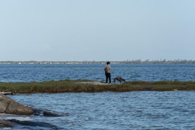 Młoda kobieta z psem pitbulla spacerująca po pasie ziemi i trawy pośrodku laguny araruama w rio de janeiro.