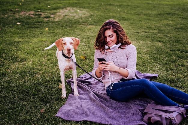 Młoda kobieta z psem w parku. kobieta używa telefon komórkowego