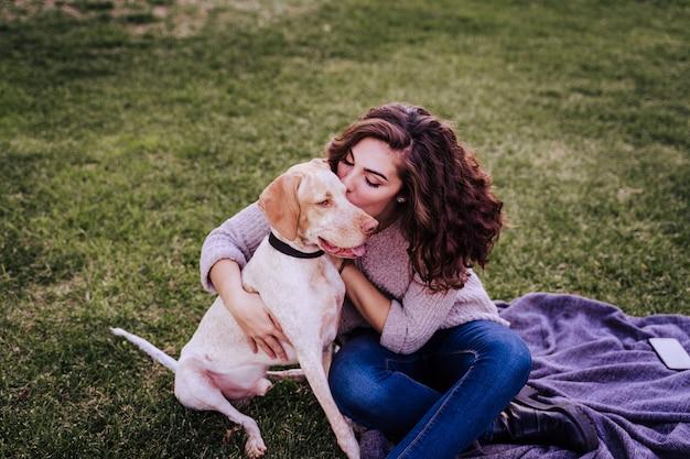 Młoda kobieta z psem w parku. ona całuje psa