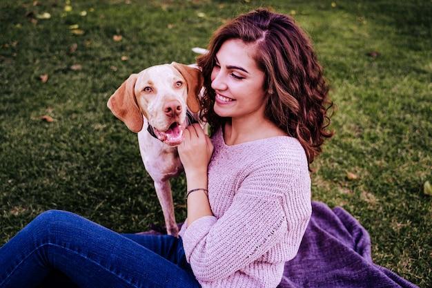 Młoda kobieta z psem w parku