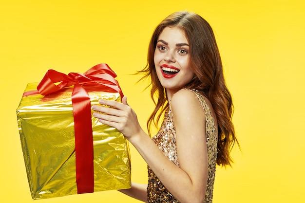 Młoda kobieta z pudełkami prezentów w jej rękach w pięknych ubraniach, sprzedaje prezenty, szczęśliwych bożych narodzeń i nowego roku