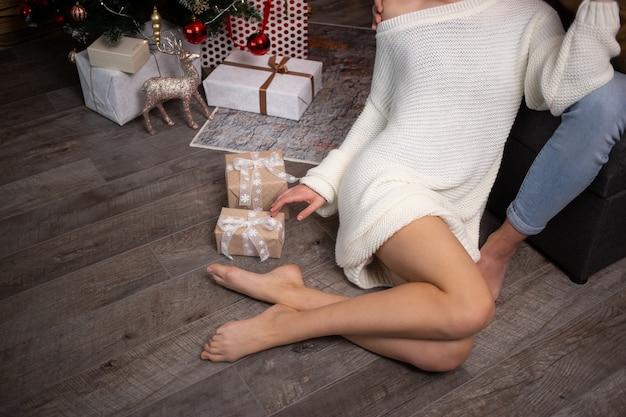 Młoda kobieta z pudełkiem, ciesząc się czasem razem z chłopakiem w domu. choinka na tle.
