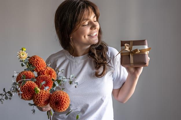 Młoda kobieta z pudełkiem prezentowym i bukietem kwiatów chryzantem