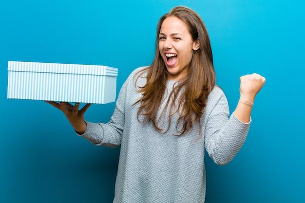 Młoda kobieta z pudełkiem przeciw błękitnemu tłu