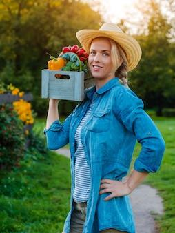 Młoda kobieta z pudełkiem świezi ekologiczni warzywa przy zmierzchem