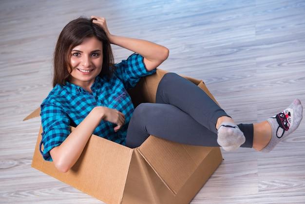 Młoda kobieta z pudełkiem w chodzenie domu pojęciu