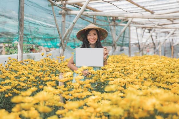 Młoda kobieta z pustą białą deską w kwiatu gospodarstwie rolnym