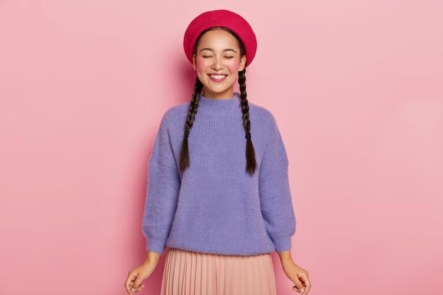 Młoda kobieta z radosnym wyrazem twarzy, z zamkniętymi oczami, nosi czerwony beret, ciepły fioletowy sweter i plecioną spódniczkę, czerpie przyjemność z otrzymywania komplementów, pozuje na różowej ścianie