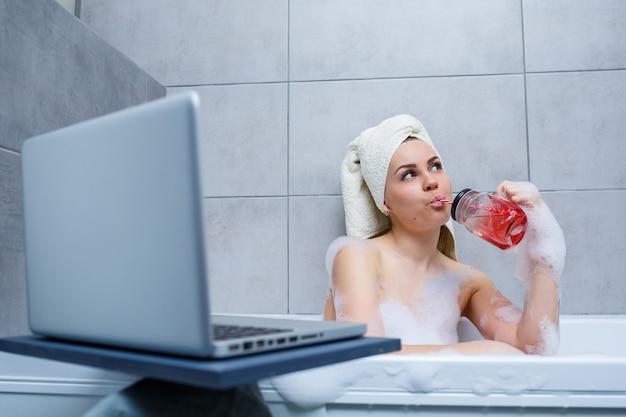 Młoda kobieta z ręcznikiem na głowie pije sok, oglądając film na laptopie, siedząc w wannie w salonie piękności. zrelaksuj się w łazience bez pościeli. koncepcja pielęgnacji ciała i relaksu.