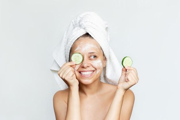 Młoda kobieta z ręcznikiem na głowie trzyma w dłoniach plasterki ogórka, aby zrobić odświeżającą maskę