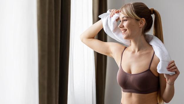 Młoda kobieta z ręcznikiem po ćwiczeniach