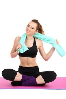 Młoda kobieta z ręcznikiem po treningu na białym tle