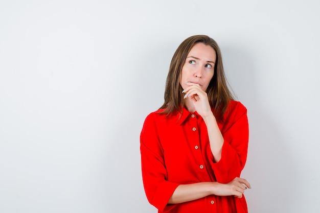 Młoda kobieta z ręką na brodzie, patrząca w górę w czerwonej bluzce i patrząca zamyślona, widok z przodu.