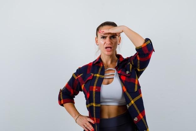 Młoda kobieta z ręką na głowie, aby wyraźnie widzieć w crop top, koszuli w kratkę, spodniach i patrząc zdziwiona, widok z przodu.