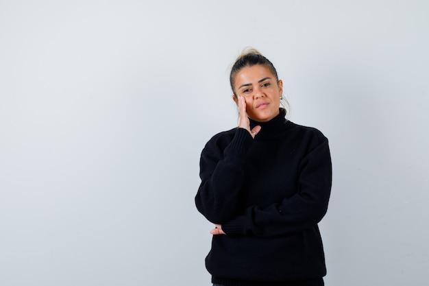 Młoda kobieta z ręką na policzku w swetrze z golfem i patrząc zamyślony. przedni widok.