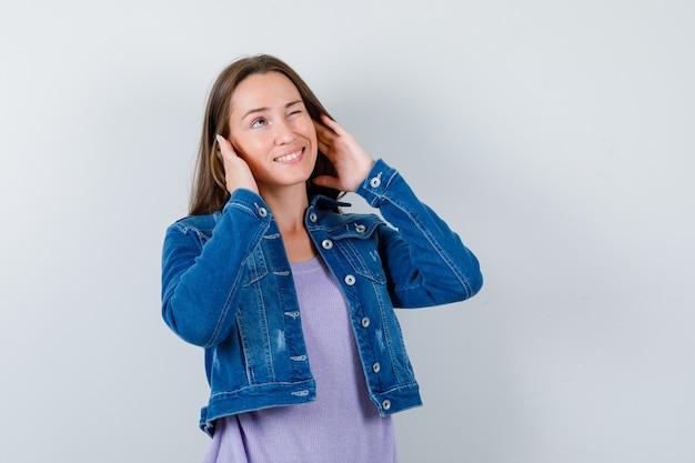 Młoda kobieta z rękami blisko uszu, patrząc w górę w koszulce, kurtce i patrząc ciekawy, widok z przodu.