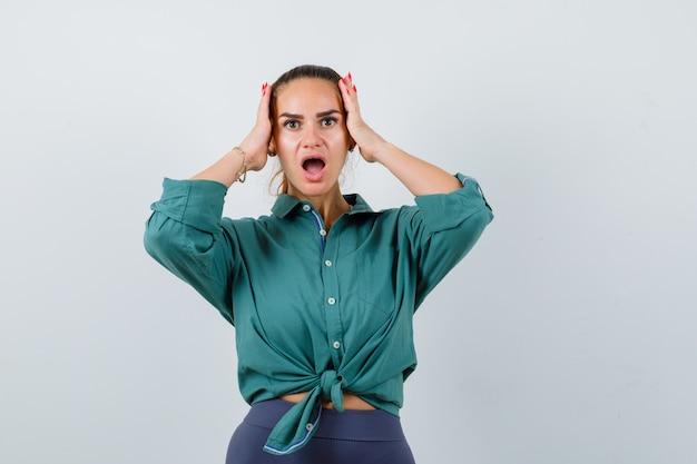 Młoda kobieta z rękami na głowie w zielonej koszuli i patrząc w szoku. przedni widok.
