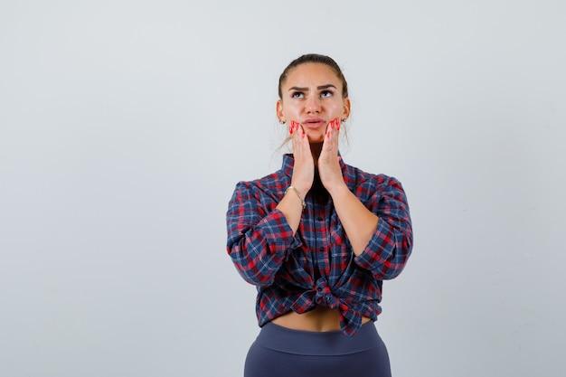Młoda kobieta z rękami na policzkach w kraciastej koszuli, spodniach i patrząc zamyślony. przedni widok.