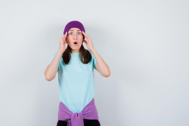Młoda kobieta z rękami na skroniach, z otwartymi ustami w niebieskiej koszulce, fioletowej czapce i wyglądająca na zszokowaną. przedni widok.