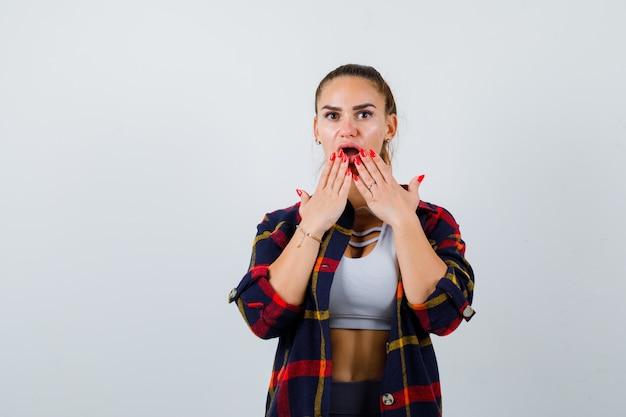 Młoda kobieta z rękami na ustach w crop top, kraciaste koszule, spodnie i patrząc zdziwiony. przedni widok.