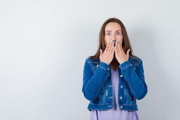 Młoda kobieta z rękami na ustach w koszulce, kurtce i patrząc się zastanawiała. przedni widok.