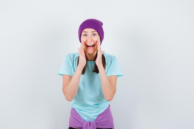 Młoda kobieta z rękami przy ustach jako mówiący sekret w niebieskiej koszulce, fioletowej czapce i wyglądającej wesoło. przedni widok.