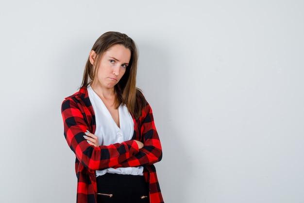 Młoda kobieta z rękoma złożonymi w ubranie i wyglądający ponuro. przedni widok.