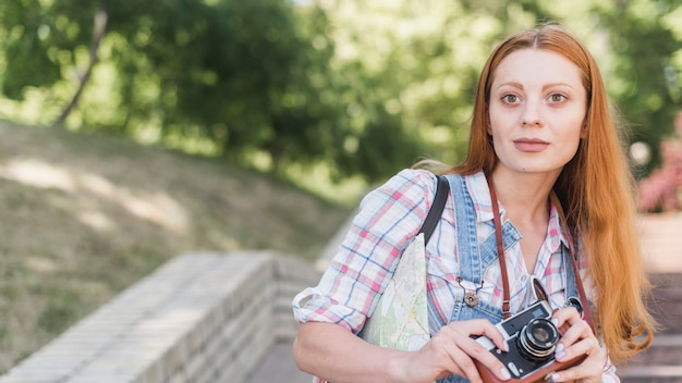 Młoda kobieta z retro kamerą w parku