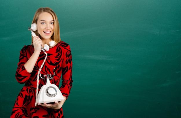 Młoda kobieta z retro telefonem odizolowywającym