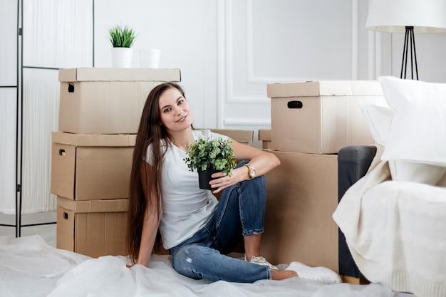 Młoda kobieta z roślin domowych siedzi na podłodze w nowym salonie