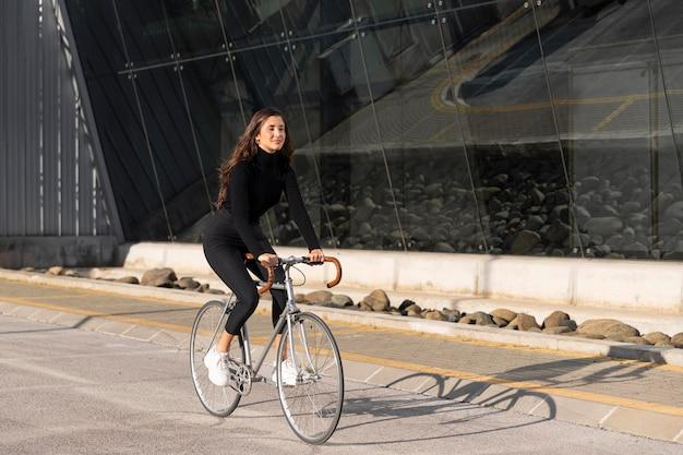 Młoda kobieta z rowerem na zewnątrz