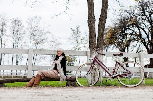 Młoda kobieta z rowerem w parku