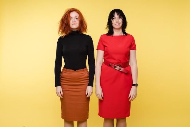 Młoda kobieta z rozczochranymi włosami pozowanie po konflikcie na białym tle na żółtym tle studio. dwie dziewczyny mody lub stylowa bizneswoman o pozytywnych emocjach