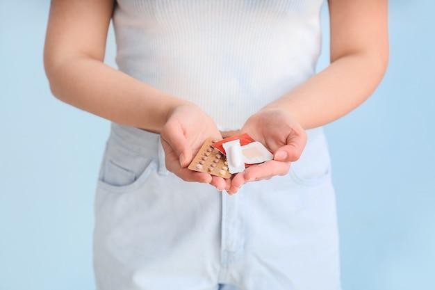 Młoda kobieta z różnymi środkami antykoncepcyjnymi na niebiesko