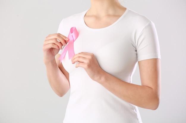 Młoda kobieta z różową wstążką na białym tle. koncepcja świadomości raka piersi
