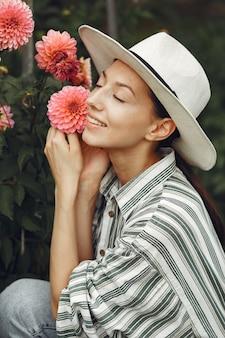 Młoda kobieta z różowymi kwiatami. pani w kapeluszu. dziewczyna w ogrodzie.