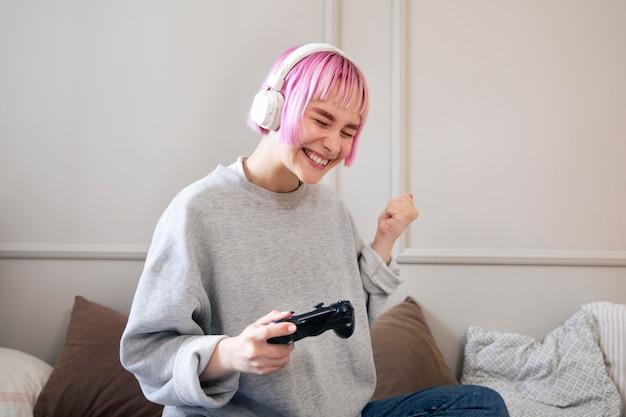 Młoda kobieta z różowymi włosami, grając w grę wideo
