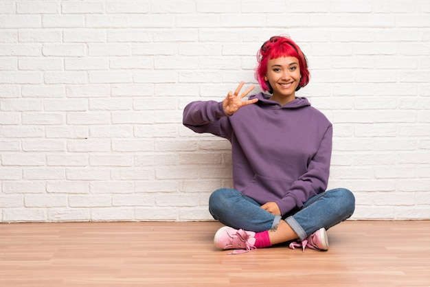 Młoda kobieta z różowymi włosami siedzi na podłodze szczęśliwy i licząc trzy z palcami