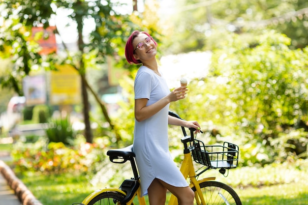 Młoda kobieta z różowymi włosami spacery po parku z rowerem, jedzenie lodów latem. środowiskowy rodzaj transportu