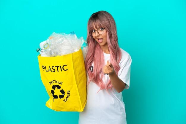 Młoda kobieta z różowymi włosami trzyma torbę pełną plastikowych butelek do recyklingu na białym tle na niebieskim tle robienia pieniędzy gest