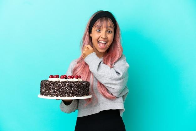 Młoda kobieta z różowymi włosami trzyma tort urodzinowy na białym tle na niebieskim tle świętuje zwycięstwo