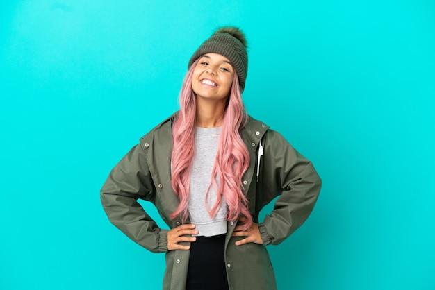 Młoda kobieta z różowymi włosami, ubrana w przeciwdeszczowy płaszcz na białym tle na niebieskim tle, pozująca z rękami na biodrach i uśmiechnięta