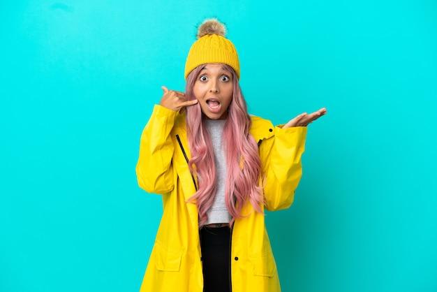 Młoda kobieta z różowymi włosami, ubrana w przeciwdeszczowy płaszcz na białym tle na niebieskim tle, wykonująca gest telefoniczny i wątpiący