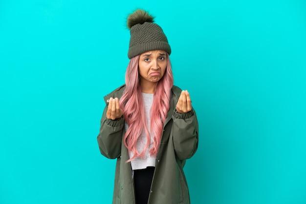 Młoda kobieta z różowymi włosami ubrana w przeciwdeszczowy płaszcz na niebieskim tle robi gest pieniędzy, ale jest zrujnowana