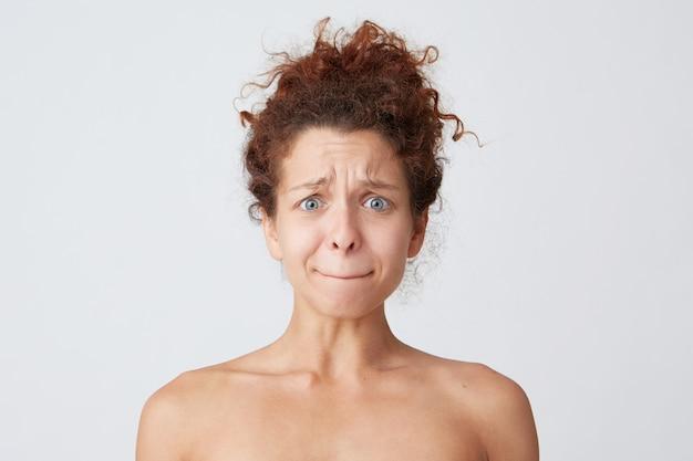 Młoda kobieta z rude kręcone włosy pozowanie i grymas